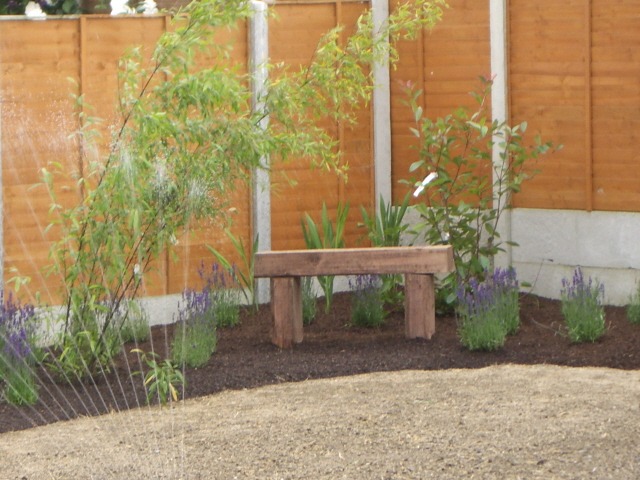 Small garden corner bed and seat simple peter donegan for Easy small garden ideas